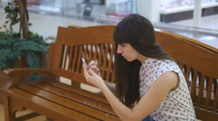 Girl sit at bench play the popular smartphone game - catching pokemon in mall Stock Footage