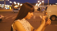 Young woman playing Pokemon GO outdoor at shopping center parking Stock Footage