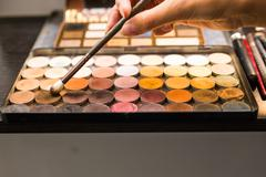 The female hands eyeshadow palette and cosmetic brush Stock Photos