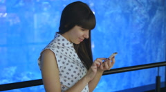 Young woman playing Pokemon GO indoor at oceanarium, using smart phone Stock Footage