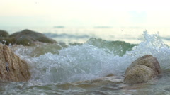 Waves crashing on stones in sea slowmotion close-up Stock Footage