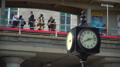 Clock with commuters waiting behind it Stock Footage