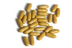 Group of Mustard Colored Capsules on White Background Stock Photos