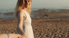 Girl in a Dress is a Man 's Hand on a Beach - stock footage