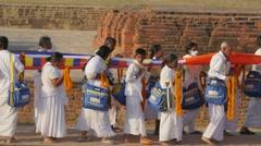 Pilgrims bringing long buddhist cloth to Dhamekh Stupa,Sarnath,India Stock Footage