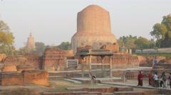 Pilgrims walking around monastery ruins with Dhamekh Stupa,Sarnath,India Stock Footage