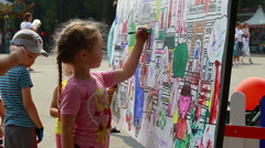 Urban park, little girl drawing on the board (Editorial). Stock Footage