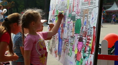 Urban park, two little girls are drawing something on the board (Editorial). Stock Footage
