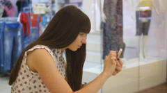 Girl play the popular smartphone game - catching pokemon in hypermarket mall - stock footage