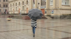 Young Girl With an Umbrella Walking in Heavy Rain in the City - stock footage
