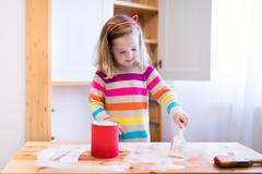 Little girl painting wooden closet Stock Photos