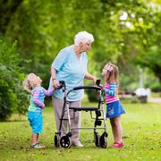 Grandmother with walker playing with two kids - stock photo