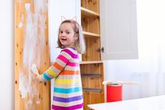 Little girl painting wooden closet - stock photo