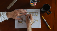Overhead of Engineer designing by hand with pencil and paper Stock Footage