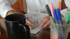 Handheld of Engineer designing by hand with pencil and paper at desk Stock Footage