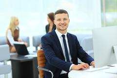 Smiling business man standing with his collegues in background a Stock Photos