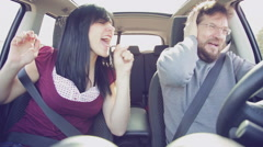 Man driving car listening girlfriend singing out of tune Stock Footage