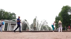 Tourists walk against Eva fountain at Peterhof Lower Gardens, slow motion Stock Footage
