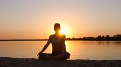 Meditation near the sea and doing yoga on a beach at sunset Stock Footage