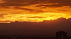 LAS VEGAS - Pan down from fiery sunset over mountain range revealing Stock Footage