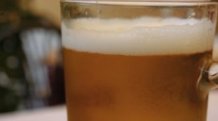 Beer glass covered in condensation perlage, bubbles rising inside Stock Footage