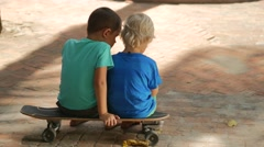 Multiracial сhildren playing online games on smart phone sitting on skateboard Stock Footage