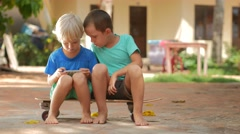 Multiracial сhildren playing online games on smart phone sitting on skateboard - stock footage