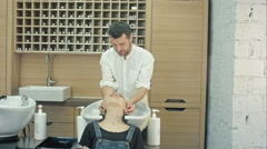 Handsome hairdresser washing female hair with concentration. He is holding a Stock Footage