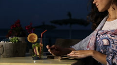 Beautiful poetess drinking refresher in beach cafe, writing novel in notebook Stock Footage