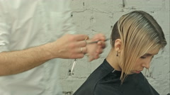 Smiling client sitting in a hair salon while hairdresser is combing her hair Stock Footage