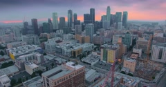 Pan across dramatic downtown Los Angeles skyline at sunset twilight dusk. 4K UHD Stock Footage