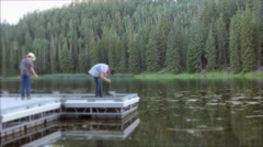 Boys fishing in a mossy mountain lake with mosquitos Stock Footage