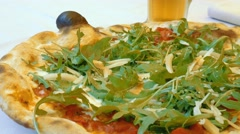 Cutting Italian Pizza topped with parmesan cheese and delicious arugula Stock Footage