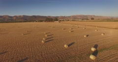 Aerial view of hay bales in field at sunset in rural California. 4K UHD. Stock Footage