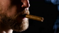 Man in a dark room, smoking a cigar. Close up - stock footage