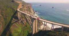 Aerial view cars passing Bixby Creek Bridge PCH Highway 1 in California Stock Footage