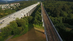 Railroad track and highway, bridges - aerial view. Passing highspeed train. Stock Footage