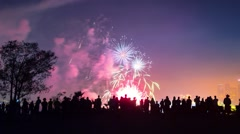 Zoom in on crowd of people silhouettes watching colorful fireworks display show Stock Footage