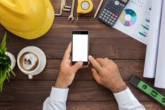 engineering using phone on his workspace top view - stock photo