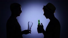 Two male friends talking and drinking beer. Back light Stock Footage