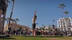Man doing cartwheel flip outdoors on lawn at Santa Monica Beach, California Stock Footage