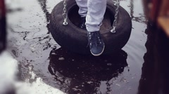 Woman having fun on tire swin on winter copy space outdoors puddle background in Stock Footage