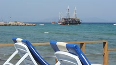 Turkish cruise boats taking tourists out , focus is on the sun loungers Stock Footage