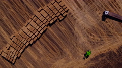 Aerial view of harvest fields with bale, tractor and forklift in sunset Stock Footage
