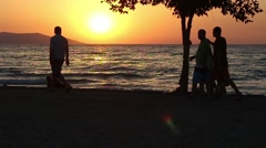 People in silhouette walking on the beach at sunset. - stock footage
