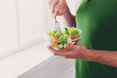Unrecognizable man has healthy lunch, eating diet vegetable salad - stock photo