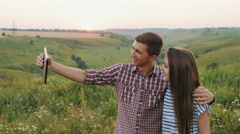 Attractive Young Girl and the Guy Taking Selfie at Sunset. Slow Motion - stock footage