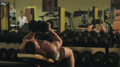 The man pumps his muscles using dumbbells lying on the bench in the gym  long sh Stock Footage