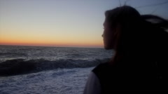Girl watching on sunrise on sea in motion Stock Footage