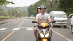 Young couple riding motor scooter stock video footage Stock Footage